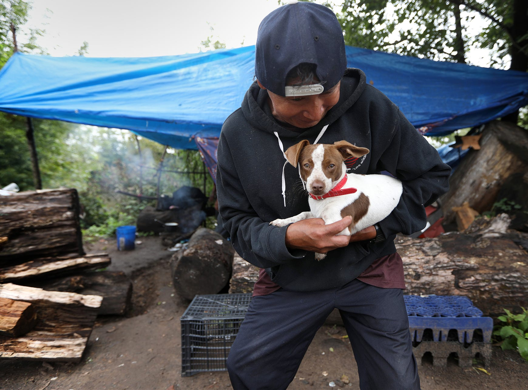 Bebe is held by Salvador Rodriguez at a homeless encampment along the Passaic River in Passaic.  Bebe lives alongside dozens of men in the area. Wednesday, September 26, 2018