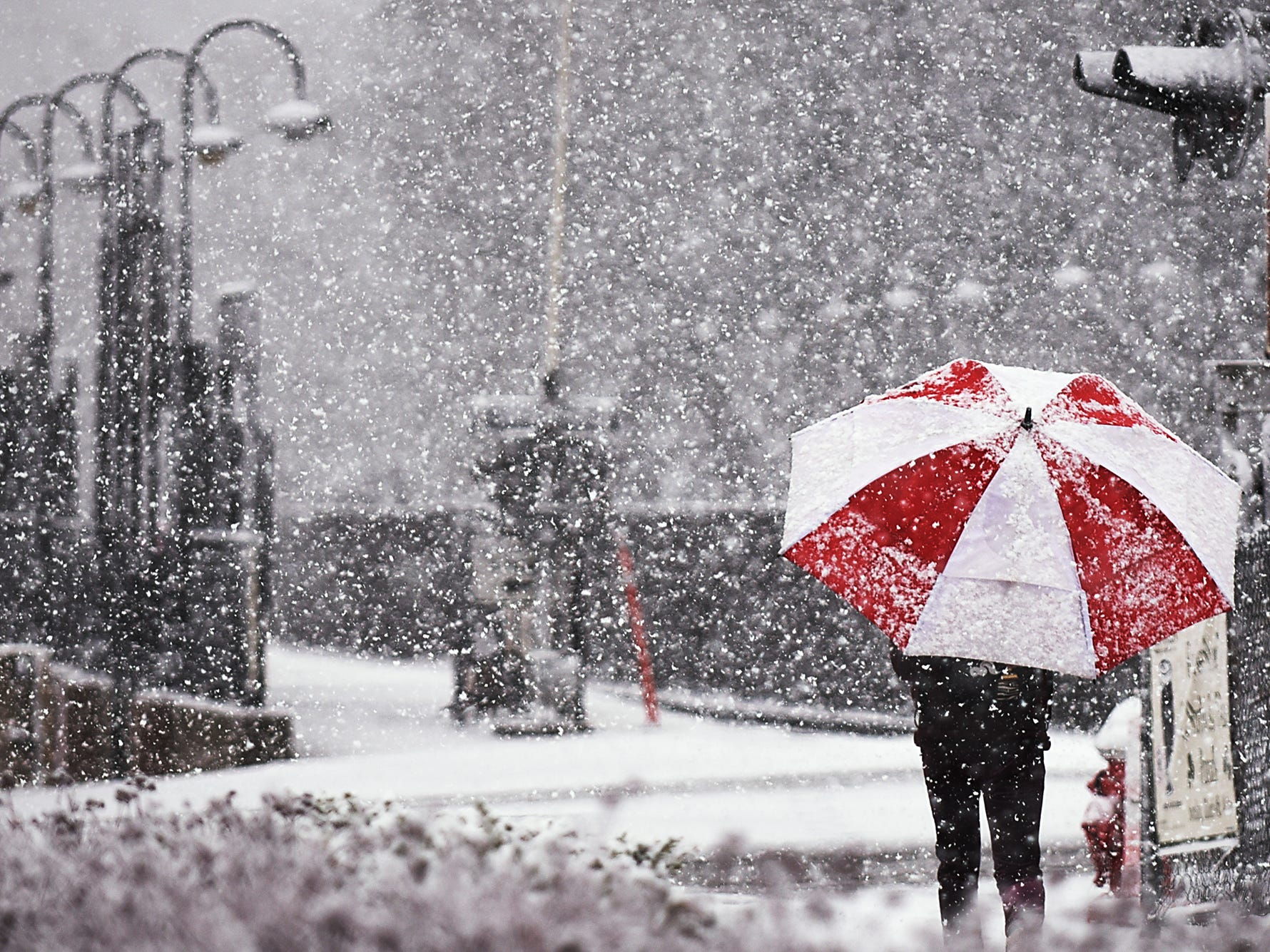 A person walks near the Rutherford train station in the Snow on Wednesday March 07, 2018.