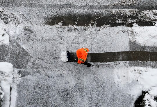 WEATHER A man shovels snow on a sidewalk in Cliffside Park, NJ.