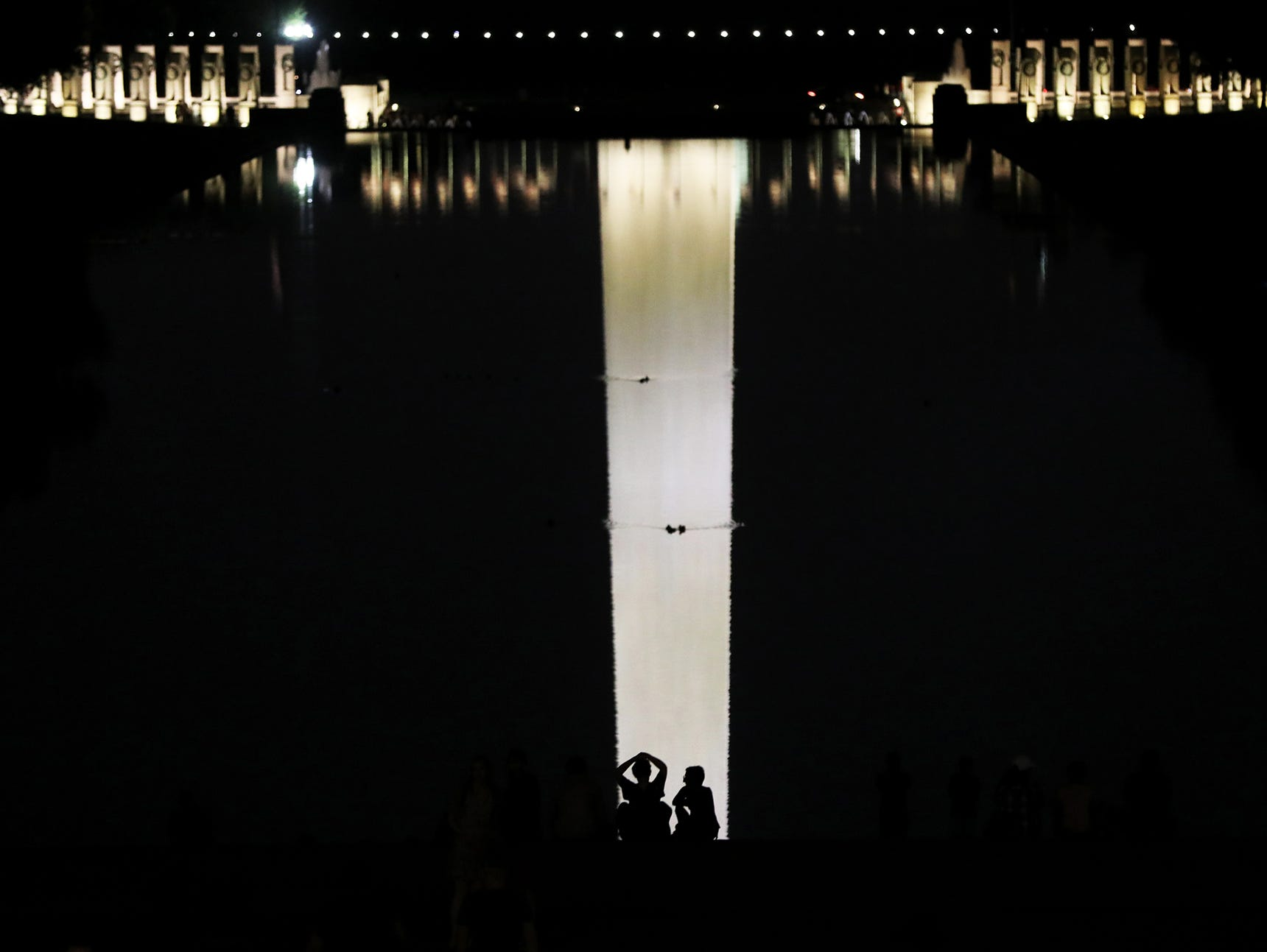 A couple is shown on the edge of the Reflecting Pool in Washington D.C. as they are silhouetted against the Washington Monument's reflection. Friday June 15, 2018