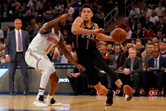 Dec 17, 2018; New York, NY, USA; Phoenix Suns guard Devin Booker (1) drives to the baskrt past New York Knicks guard Emmanuel Mudiay (1) during the first half at Madison Square Garden.