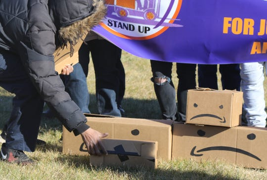 Labor advocates flip the Amazon logo upside down as part of a protest outside the Amazon Fulfillment warehouse in Robbinsville, New Jersey on December 18, 2018 to demand better protections for those working in Amazon warehouses.