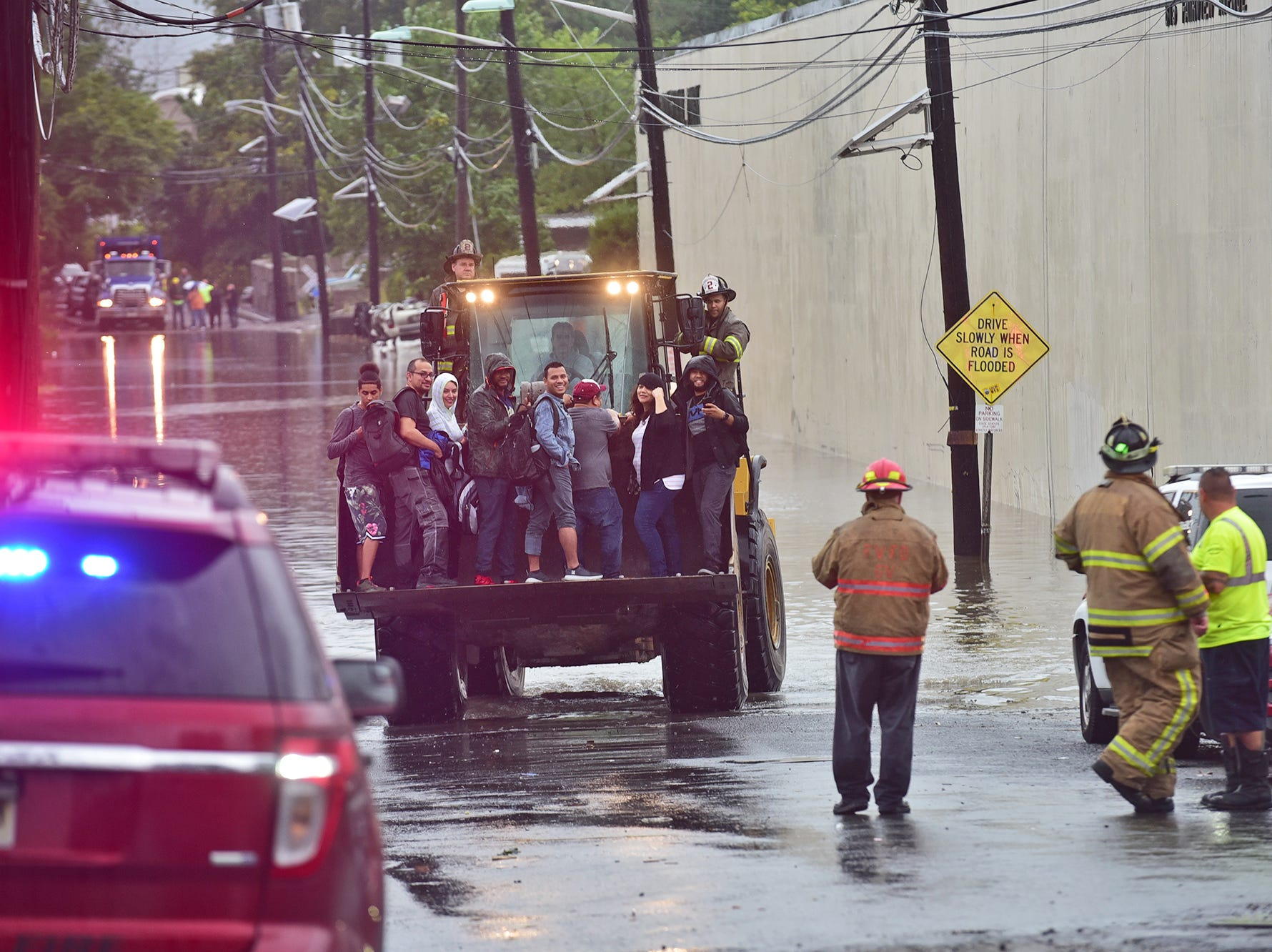BREAKING NEWS/ WEATHER Rescue personnel evacuate stranded workers with a bulldozer after high water flooded the surrounding streets at an Industrial Park in Fairview.