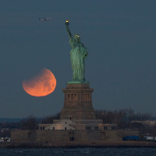 A lunar eclipse gives the moon a reddish glow over New York City on the morning of Jan. 31, 2018.