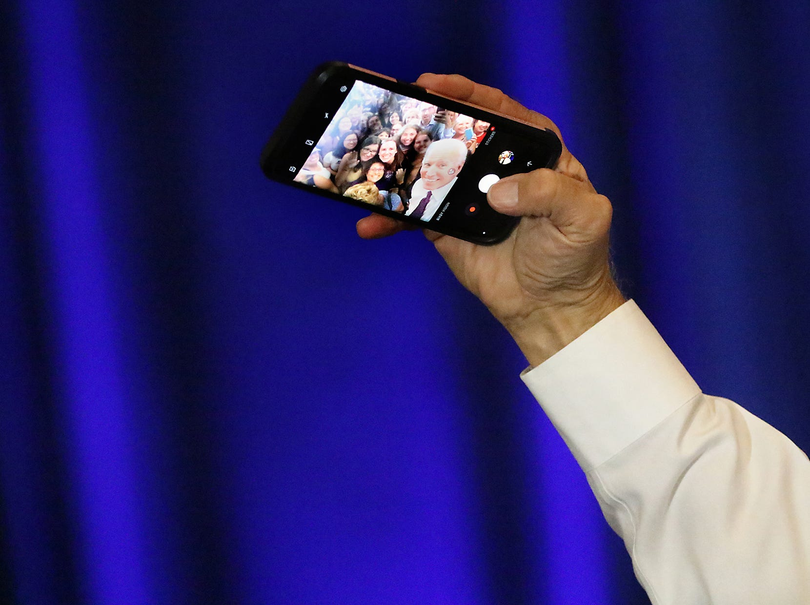 Joe Biden holds a supporters phone as he takes a selfie at Montclair State University. Wednesday, September 5, 2018