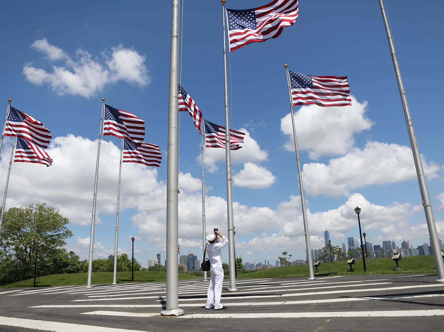 Petty Officer First Class, Carlos Vazquez, of Paterson, takes pictures of flags while in Liberty State Park.  Vazquez was in Jersey City to take pictures of ships coming up New York Harbor for Fleet Week. Wednesday, May 23, 2018