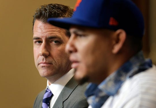 New York Mets general manager Brodie Van Wagenen, left, watches as catcher Wilson Ramos speaks during a news conference at Citi Field, Tuesday, Dec. 18, 2018, in New York.