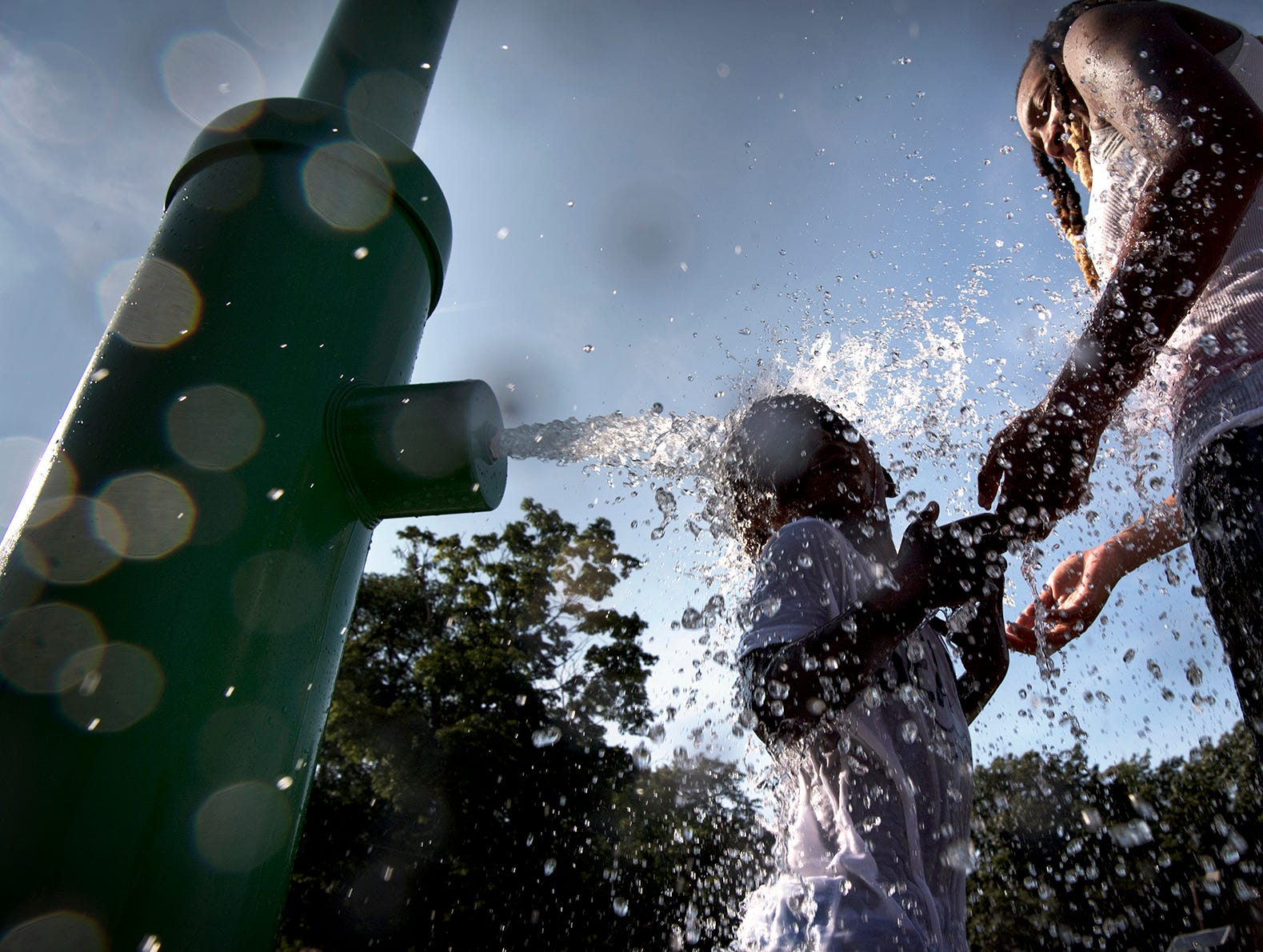 Nayah Wilson looks on as her son LJ, 4, plays in a spray of water at Polifly Road Park in Hackensack on Tuesday, August 28, 2018.