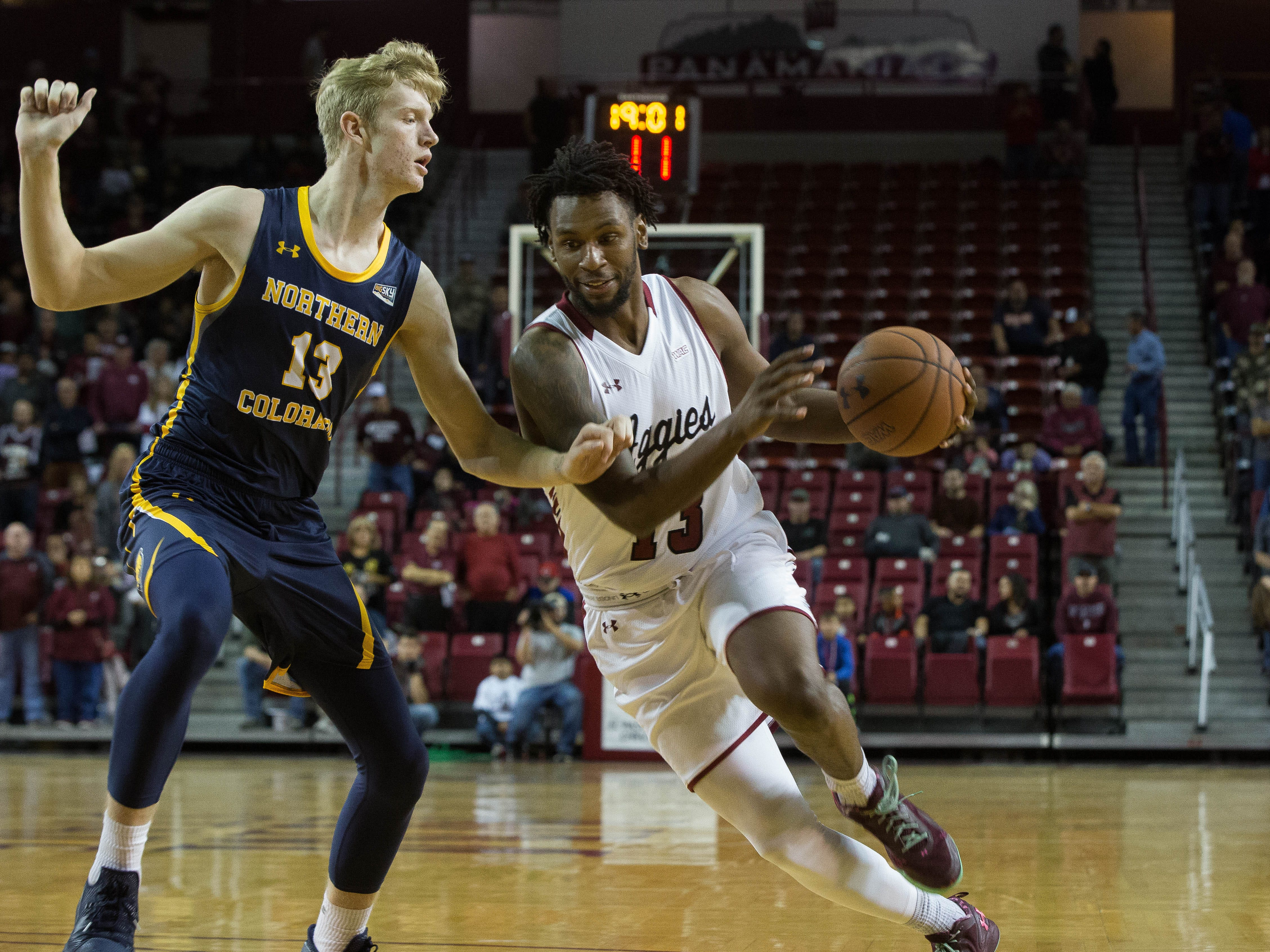 New Mexico State University's C.J. Bobbitt, drives to the basket past Northern Colorado's Bodie Hume on Monday at the Pan American Center.