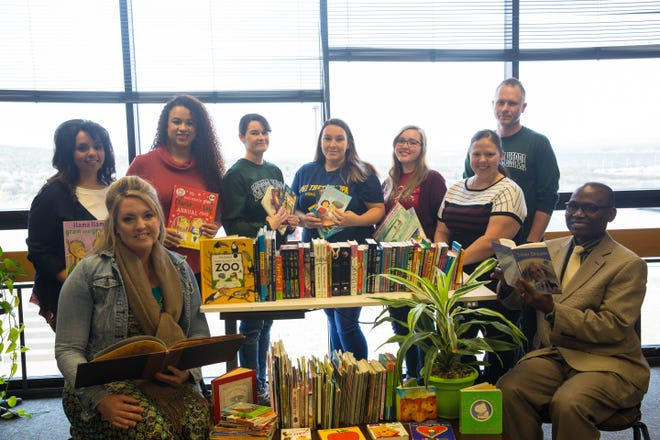 PTK students, PTK advisor Misty McCormack,Dr. AndrewNwanne, andKelli Barta of the Boys and Girls Club surrounded by donated books.