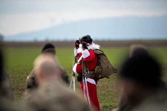 Santa Claus cheers as he completes a military freefall jump during Operation Toy Drop 2018 over Alzey Drop Zone, Germany, Dec. 12, 2018. Santa and his elves jumped from 86th Airlift Wing Super Hercules aircraft and delivered gifts to children.