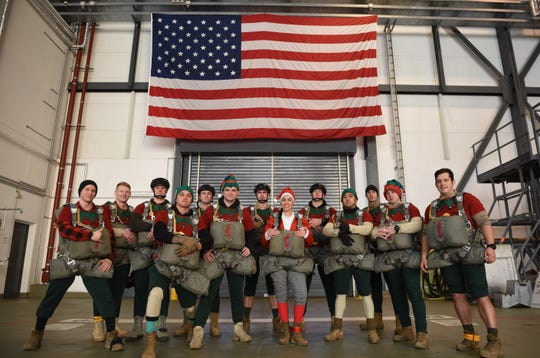 Mrs. Claus poses with 12 of Santa's elves for a photo after being rigged into their parachutes for Operation Toy Drop 2018 at Ramstein Air Base, Germany, Dec. 13, 2018. Members of the 5th Quartermaster Theater Aerial Delivery Company worked with the 435th Air Ground Operations Wing, 86th Airlift Wing, and seven coalition partners. (