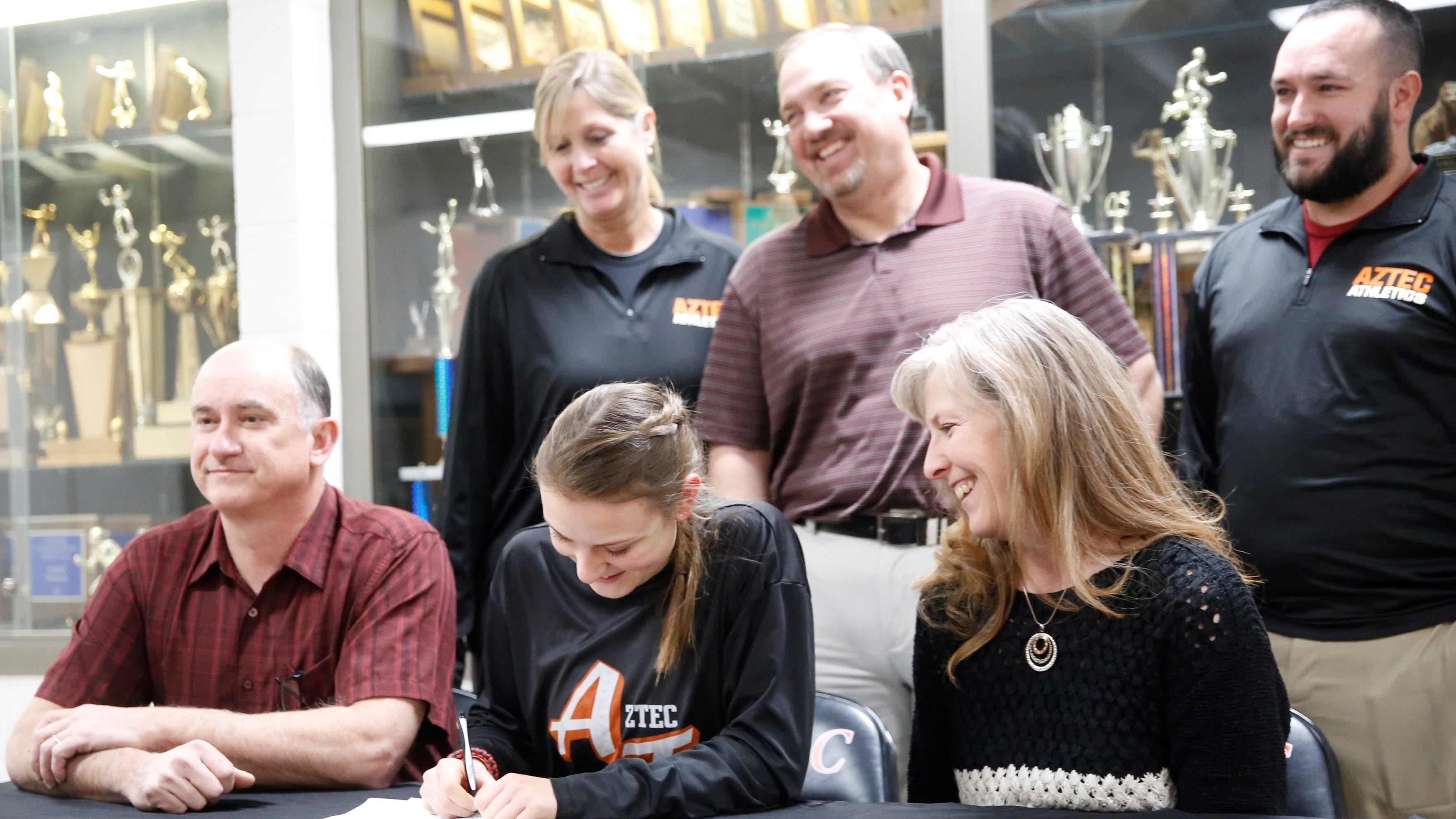Aztec's Hailey Chapman signs her letter of intent on Tuesday to continue her cross country and track career at NCAA Division II Holy Names University.