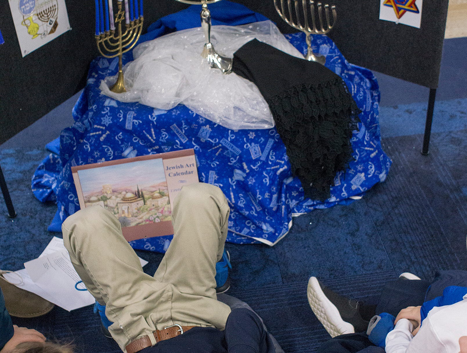 Brady MacMartin makes himself comfortable while learning about Hanukkah, the Festival of Lights.