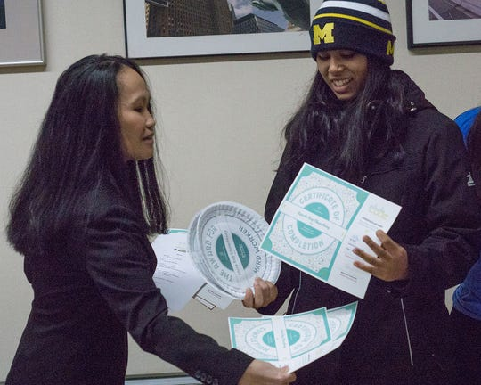 Girls Who Code co-founder Ny Derry presents awards to Ayushi Chowdhury, a student at International Academy in Troy.