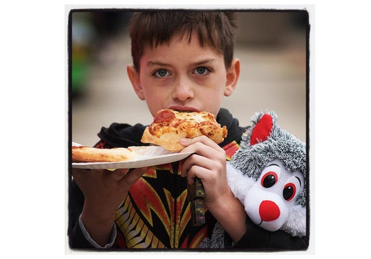 Plymouth's Fall Festival is all about the food. Robert Lawfield, 8 years old, of Canton, works on a couple scices of pizza. It looks like he won a prize, too.