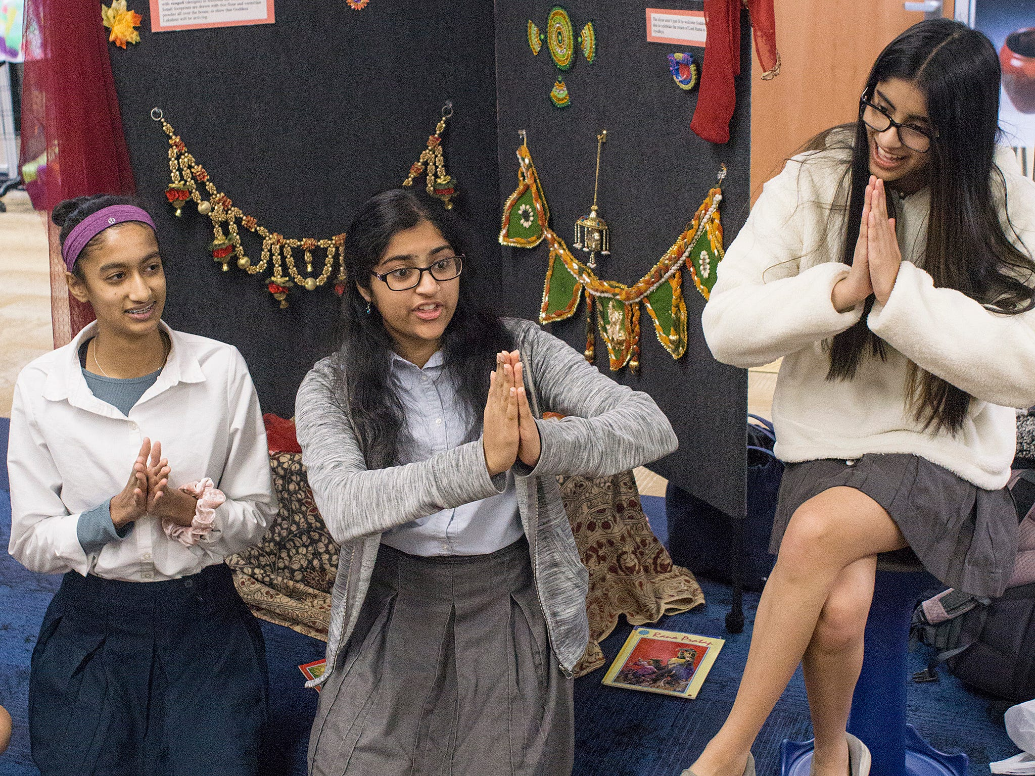 """Shreya Chalasani, Sahithi Oruganti, and Tara Nayak teach the second graders the traditional greeting associated with the Hindu religion, """"Namaste"""", which means """"I bow to you""""."""