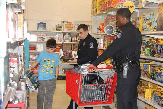Novi Police officers Jacob Roberts and Officer Jerry Webb shop with a youngster at Target.