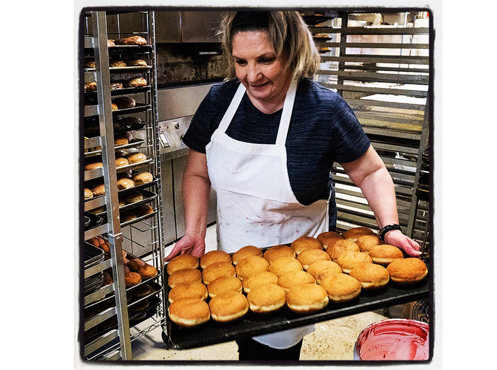 The Livonia Heritage Bakery crew began making paczki on Sunday for the annual celebrations on Fat Tuesday, the day before the beginning of Lent. Stojka Grezlovska brings another tray up front for customers waiting in line on Monday afternoon. Livonia, Michigan.