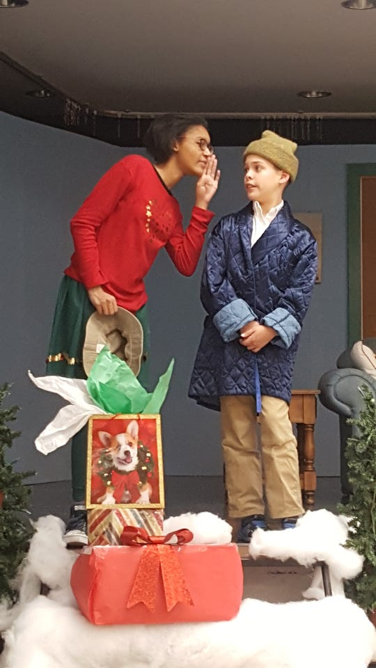 The Ghost of Christmas Presents (Alexandra Halliburton) tells Scrooge (Ben Fleming) a secret.