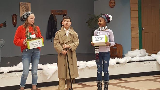 Felicity (Jackie Friedrichs, left) and Charity (Jayla Simmons) try to get the miserly Scrooge (Ben Fleming) to donate to their causes.