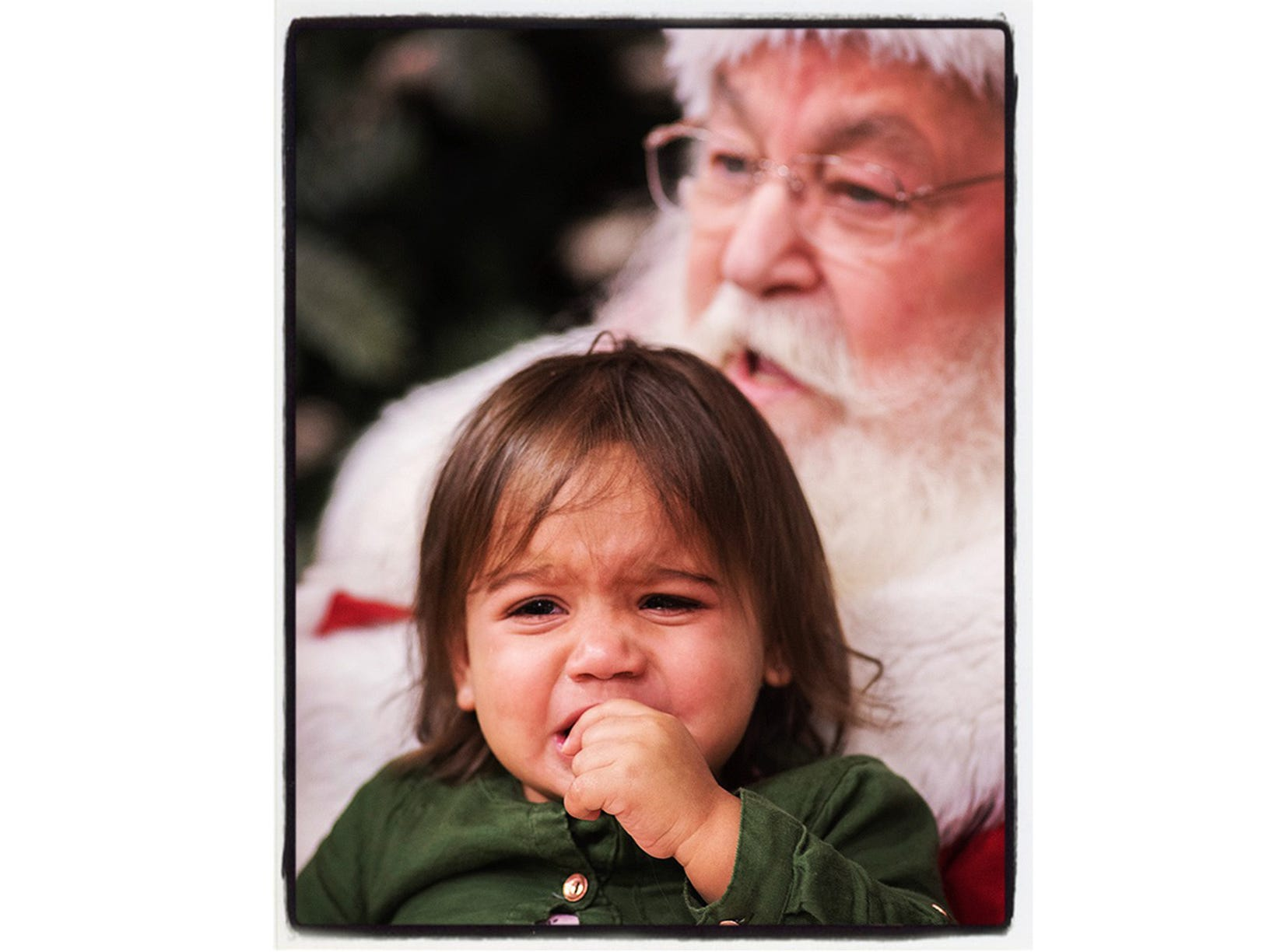 Fifteen month old Brynn McRae isn't real sure about the old bearded guy in the red suit. Canton Twp, Michigan.