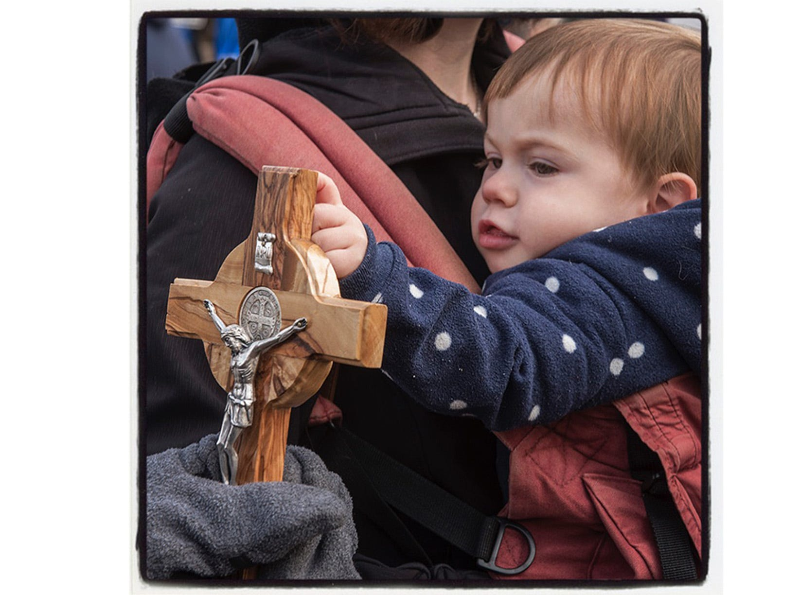One year old Eamon Kovacs touches a crucifix held by an Planned Parenthood clinic protester. Eamon is held by his mother, Elizabeth Kovacs. Livonia, Michigan.