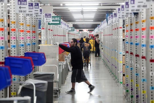 Pickers place items from individual orders in yellow binds at the Amazon Fulfillment Center in Moreno Valley before shipping on Thursday, December 13, 2018.