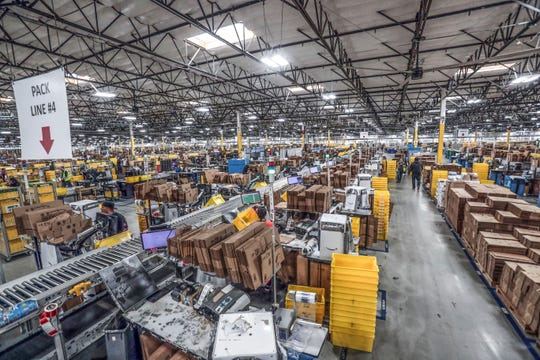 Workers package orders gathered by pickers at the  Amazon Fulfillment Center in Moreno Valley before shipping on Thursday, December 13, 2018.
