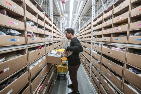 Kevin Johnson, a member of the pick-team at the Amazon Fulfillment Center in Moreno Valley, take items from shelves and place them into the yellow bins to fill orders on Thursday, December 13, 2018.