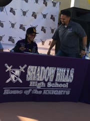 Cross country and track star Nyah Chavez signs her letter of intent as cross country coach Richie DeTamble looks on.