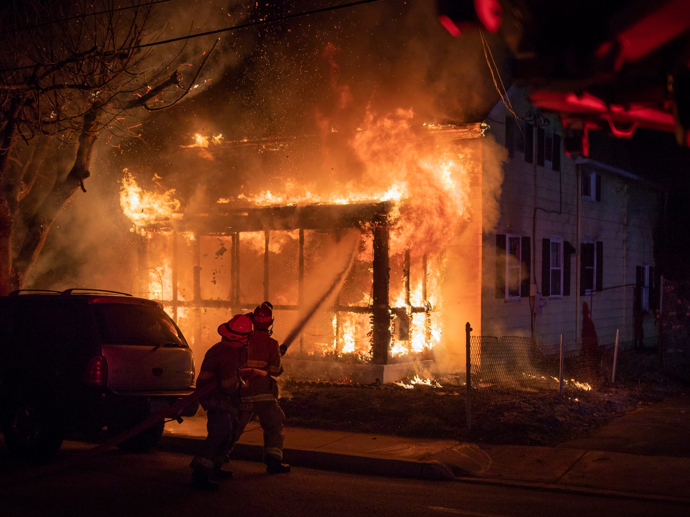 Captain Geoff Miller, right, hoses down a fully involved porch while backed up by junior firefighter Gabe Cromer, 15,  at the scene of a second-alarm house fire on the 800 block of West Middle Street, Saturday, March 17, 2018 in Hanover. No one was injured in the blaze, which came just hours after another house exploded in a three-alarm fire in Hanover.