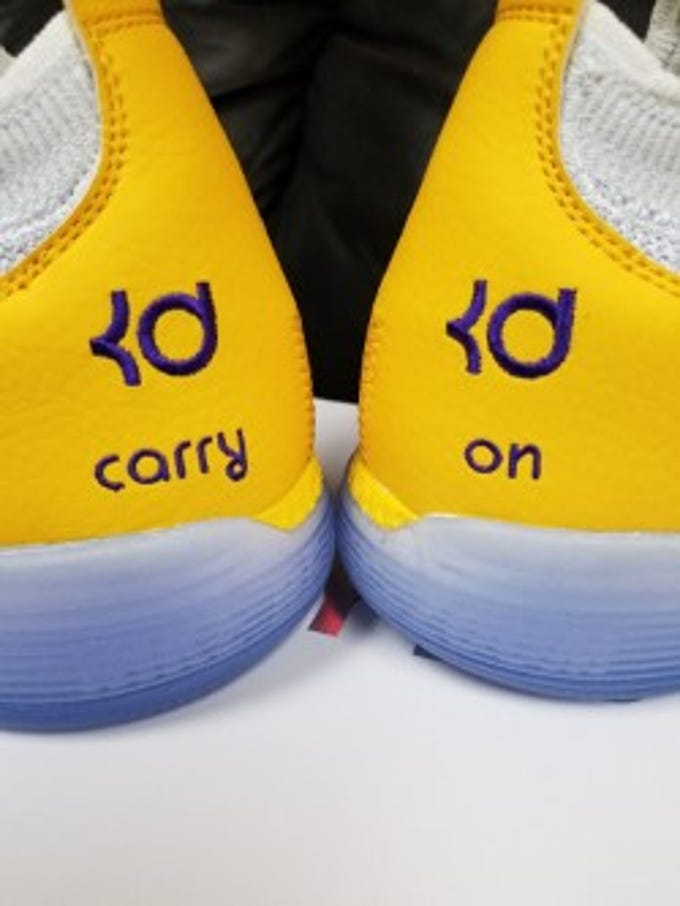 "Mesa basketball team's shoes with ""Carry On"" stitching."