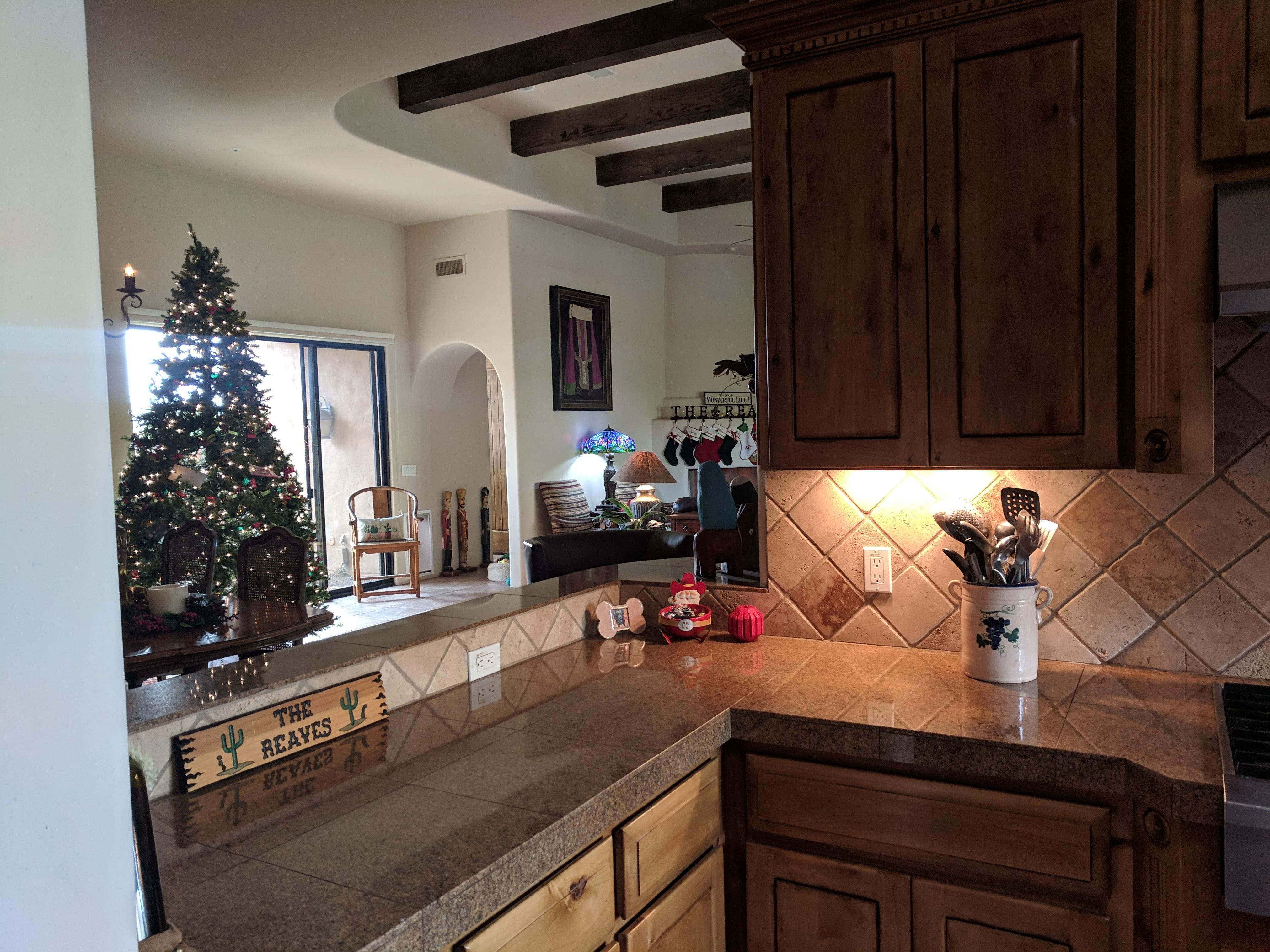 The kitchen area provides a peek-through to the living area, which is decorated for Christmas.