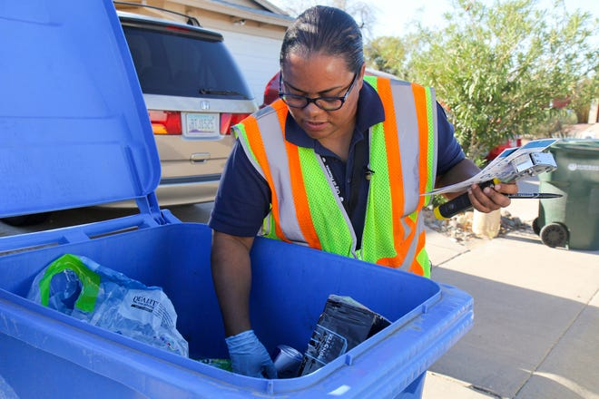 Monica Strauss, a Phoenix Public Works employee, digs through a resident's recycling to determine how much can actually be recycled. It's part of a new city effort to help people understand what they can and cannot recycle.  (Photo by Stephanie Morse/Cronkite News)