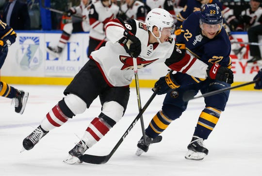 Buffalo Sabres forward Johan Larsson (22) and Arizona Coyotes forward Michael Bunting (58) battle for position during the second period of an NHL hockey game, Thursday, Dec. 13, 2018, in Buffalo N.Y. (AP Photo/Jeffrey T. Barnes)