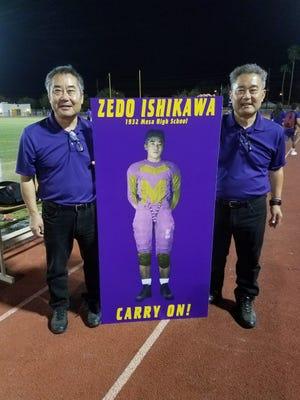 Mark Ishikawa (left) and twin brother Brian Ishikawa stand with a poster of their uncle, Zedo Ishikawa.