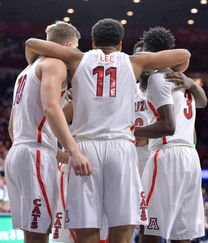 Arizona Wildcats forward Ryan Luther (10) forward Ira Lee (11) and guard Dylan Smith (3) huddle during the first half against the Baylor Bears at McKale Center. Casey Sapio-USA TODAY Sports