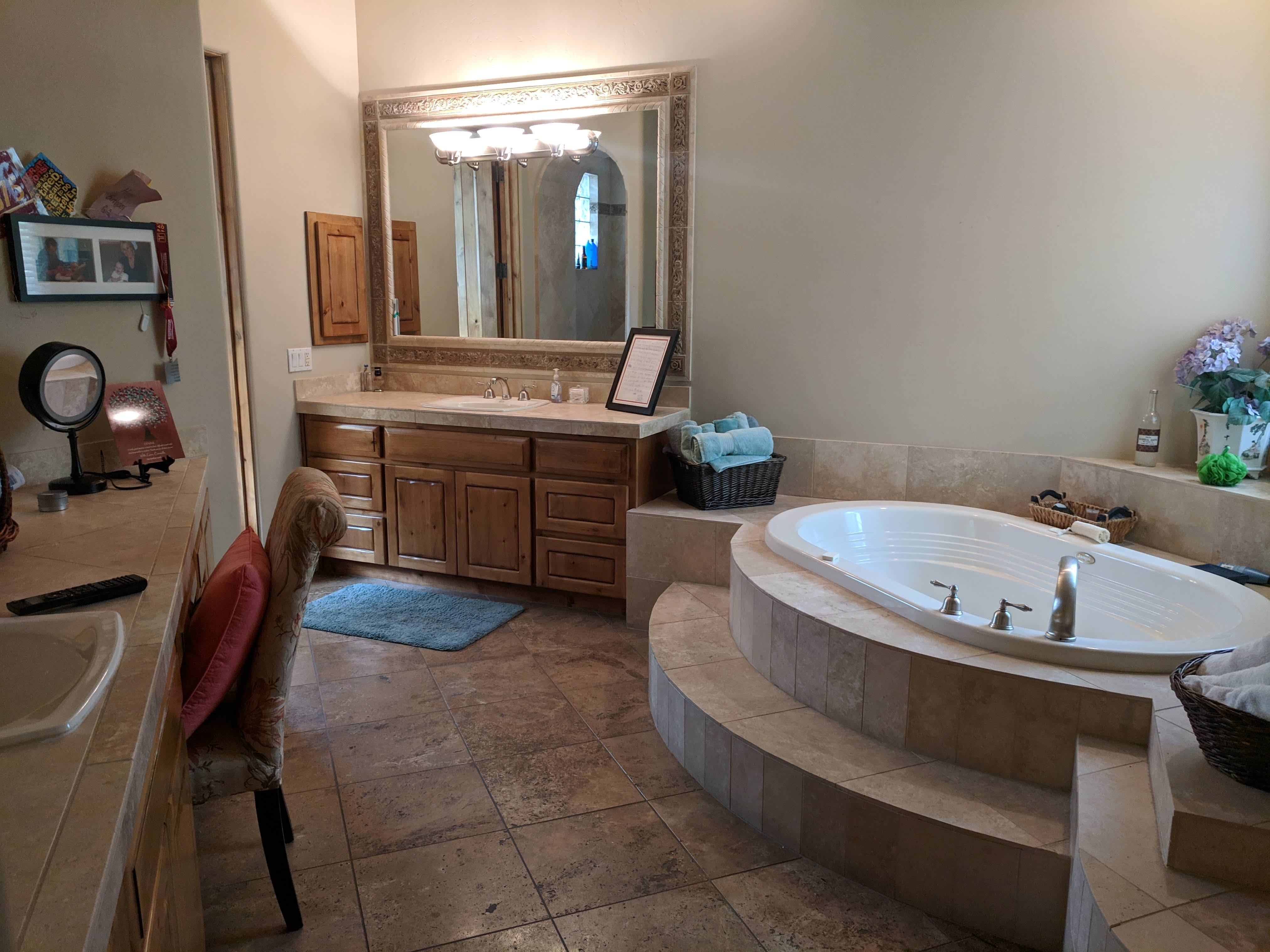 The spacious master suite features a raised soaking tub and a his and her vanity.