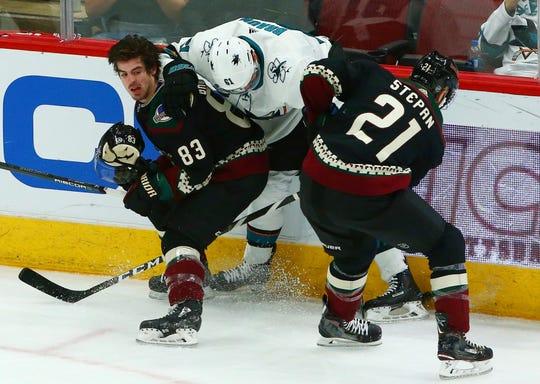 Arizona Coyotes right wing Conor Garland (83) loses his helmet as San Jose Sharks defenseman Justin Braun (61) and Coyotes center Derek Stepan (21) battle for the puck during the third period of an NHL hockey game, Saturday, Dec. 8, 2018, in Phoenix. The Sharks defeated the Coyotes 5-3. (AP Photo/Ross D. Franklin)