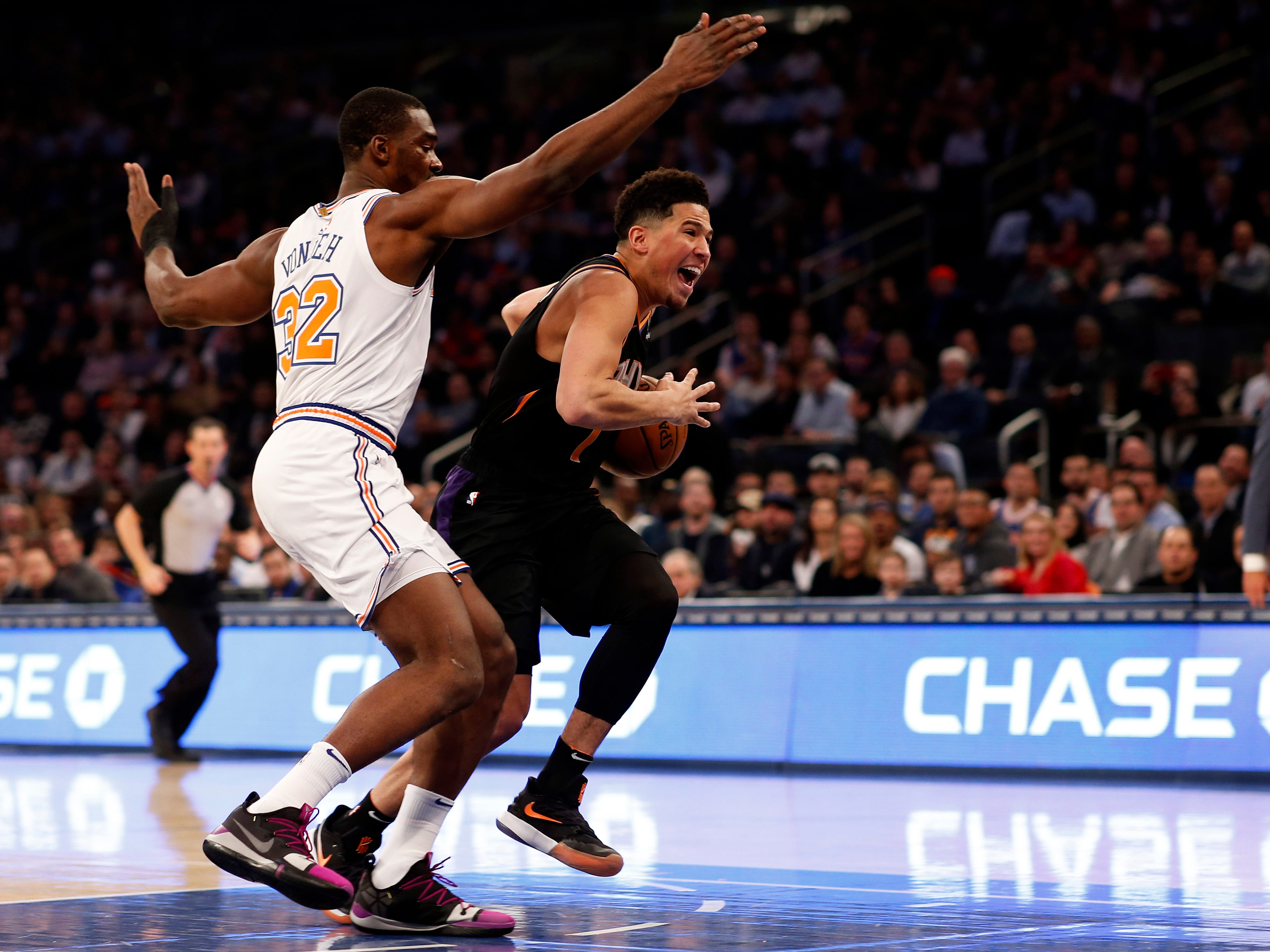 Dec 17, 2018; New York, NY, USA; Phoenix Suns guard Devin Booker (1) drives to the basket past New York Knicks forward Noah Vonleh (32) during the first half at Madison Square Garden. Mandatory Credit: Adam Hunger-USA TODAY Sports
