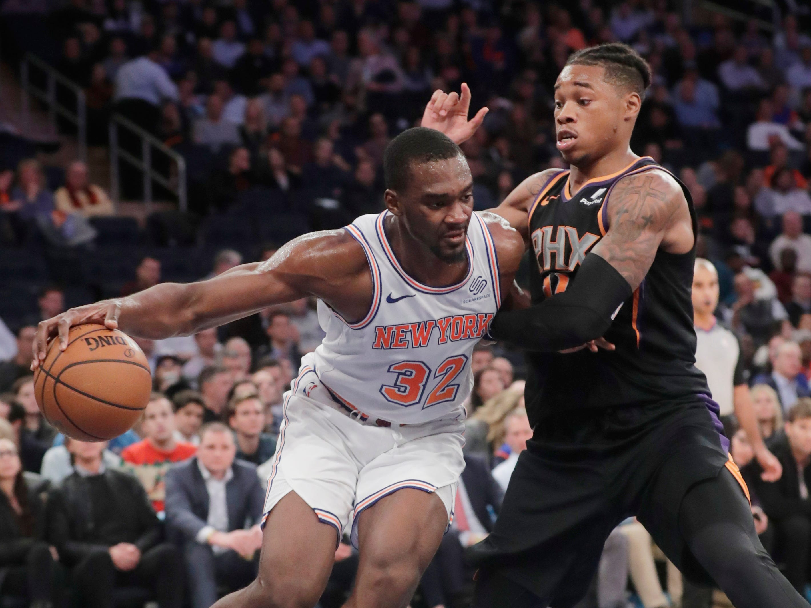 Phoenix Suns' Richaun Holmes, right, defends against New York Knicks' Noah Vonleh (32) during the second half of an NBA basketball game Monday, Dec. 17, 2018, in New York.