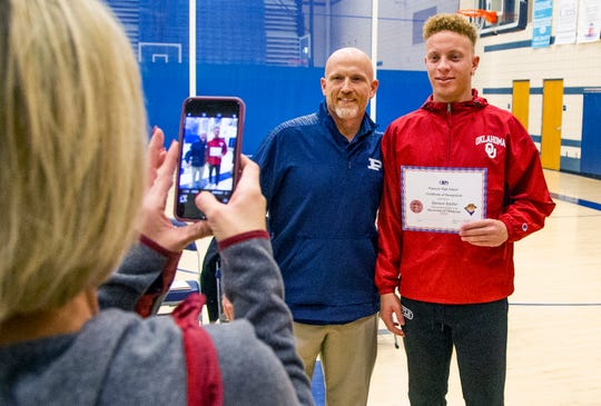 Spencer Rattler was honored with fellow Pinnacle students at a ceremony at the school on Tuesday, Dec. 18, 2018. Susan Rattler, mother of Spencer, takes a photo of football coach Dana Zupke with Spencer.