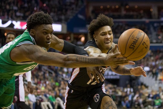 Boston Celtics center Robert Williams (44) and Washington Wizards forward Kelly Oubre Jr. (12) go for the loose ball during the second half of an NBA basketball game Wednesday, Dec. 12, 2018, in Washington. The Celtics won 130-125 in overtime. (AP Photo/Alex Brandon)