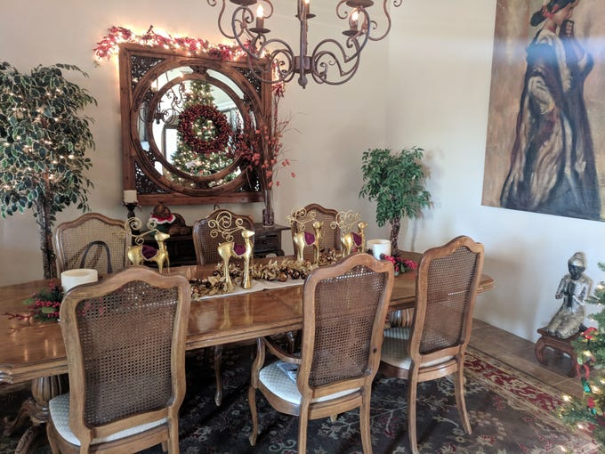 The dining area in the Reaveses' home includes a vintage window pane from China, which they backed with a mirror.