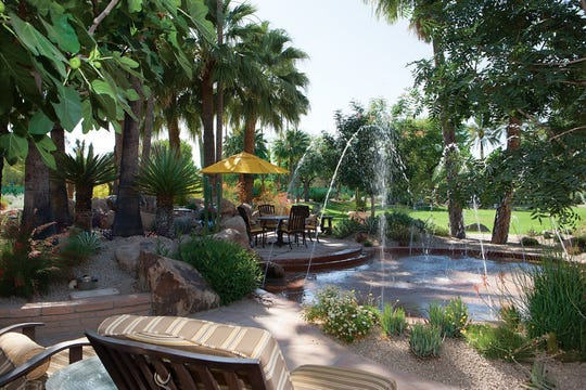 This Paradise Valley estate features grounds that include a koi pond, putting green, sport court and a walking path.