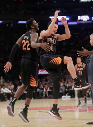 Phoenix Suns' Devin Booker (1) celebrates with teammate Deandre Ayton (22) during the second half of an NBA basketball game against the New York Knicks Monday, Dec. 17, 2018, in New York. The Suns won 128-110.