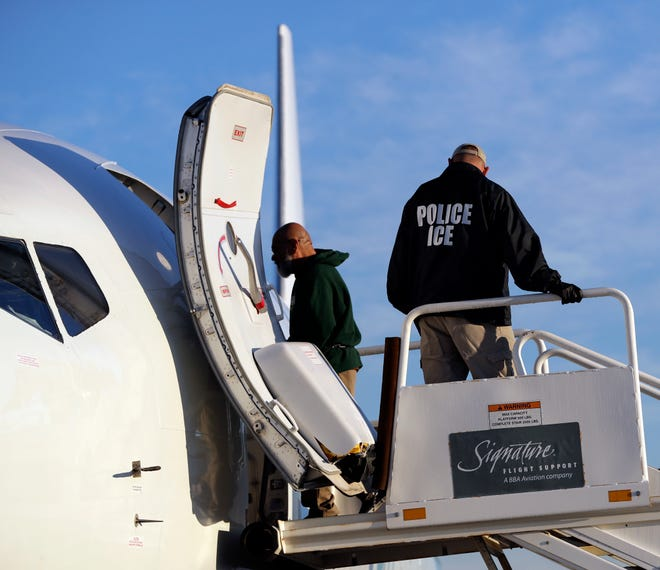 Inmigrantes indocumentados suben a un avión escoltados por ICE, para ser deportados.
