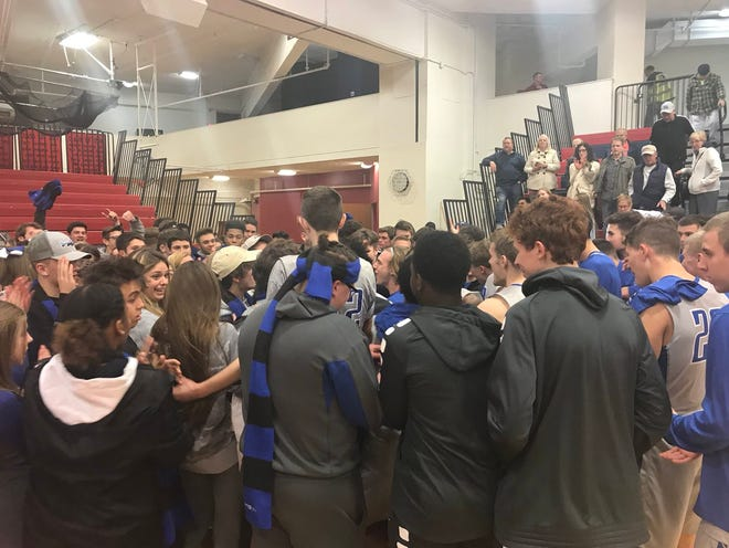 The Cedar Crest boys basketball team celebrates with its student section of supporters after Monday night's 56-46 win over Lebanon.
