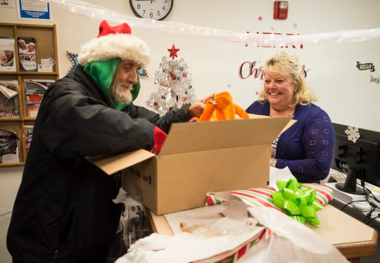 "Pam McDougal, right, watches Tommy ""Spoonman"" Woodard sort through a box full of festive hats Tuesday, Dec. 18, 2018 in the Public Guardian Office in the St. Clair County Courthouse. McDougal collected the novelty hats to give to Woodard."